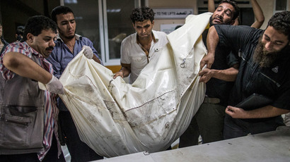 Palestinian volunteers at Gaza City's al-Shifa hospital load a body bag with the remain of children on a stretcher, on July 21, 2014 (AFP Photo / Marco Longari)