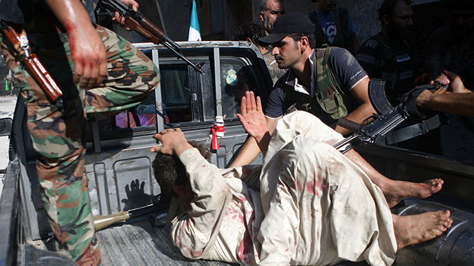"Rebel Free Syrian Army (FSA) fighters capture a policeman who the FSA allege is a ""Shabiha"" or pro-regime militiaman, on July 31, 2012, as the rebels overran a police station in Aleppo (AFP Photo)"
