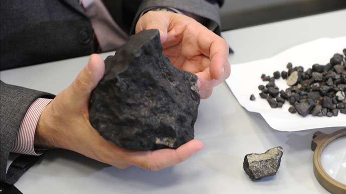 Lecturer at Ural Federal University's Institute of Physics and Technology Viktor Grokhovsky with meteorite fragment found during an expedition in the Chelyabinsk region on February 25, 2013. (RIA Novosti / Pavel Lysizin)