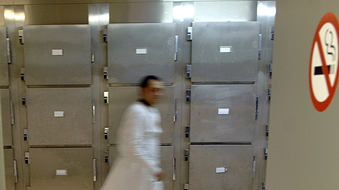 Forensic assitant walks through a cold chamber in a mortuary. (AFP Photo / Stephan Agostini)