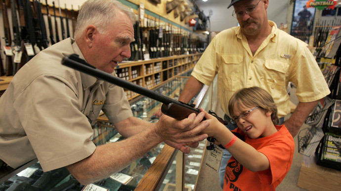 Hunter McConathy (C), 7, holds a hunting rifle with a short stock as his father Bryan (R) and Cabela's salesman Russ Duncan (L) watch him at the Cabela's store in Fort Worth, Texas (Reuters/Jessica Rinaldi)
