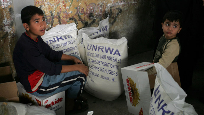 Palestinians collect food aid from the United Nations Relief and Works Agency (UNRWA) in the Rafah refugee camp, southern Gaza Strip (AFP Photo/Said Khatib)