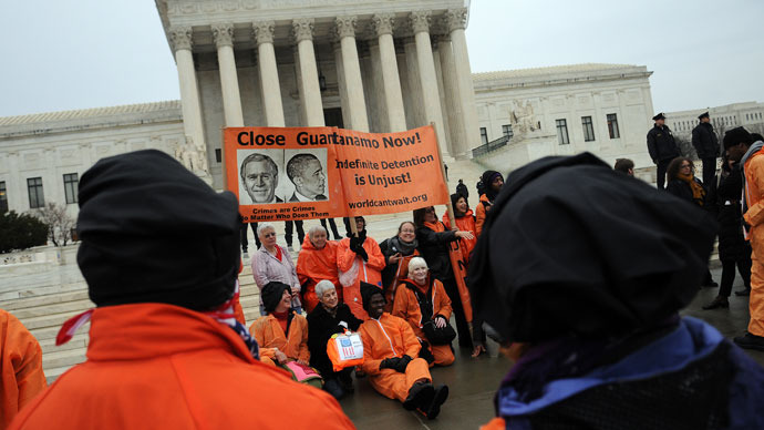Members of the organization Witness Against Torture, some of them wearing orange prison jump suits with handcuffs and a hood over their heads, end their demonstration urging the government to close down the detention facility at Guantanamo Bay, outside the U.S. Supreme Court January 11, 2012.(AFP Photo / Astrid Riecken)