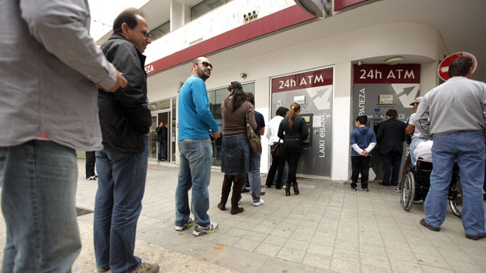 Cypriots and foreigners wait in line to withdraw money from an ATM of a Laiki (Popular) Bank branch in the old city of the capital, Nicosia.(AFP Photo / Patrick Baz)