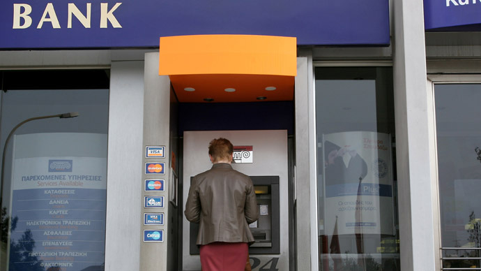A woman withdraws money from the ATM of a bank in the Cypriot capital Nicosia (AFP Photo)