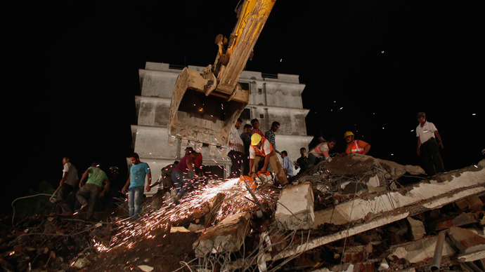 Rescue workers use a cutting tool to search for survivors after a residential building collapsed in Thane, on the outskirts of Mumbai April 4, 2013 (Reuters / Danish Siddiqui)