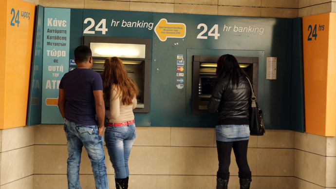 People withdraw money from a cash machine of a Bank of Cyprus branch in the capital, Nicosia, on April 8, 2013.  (AFP Photo)