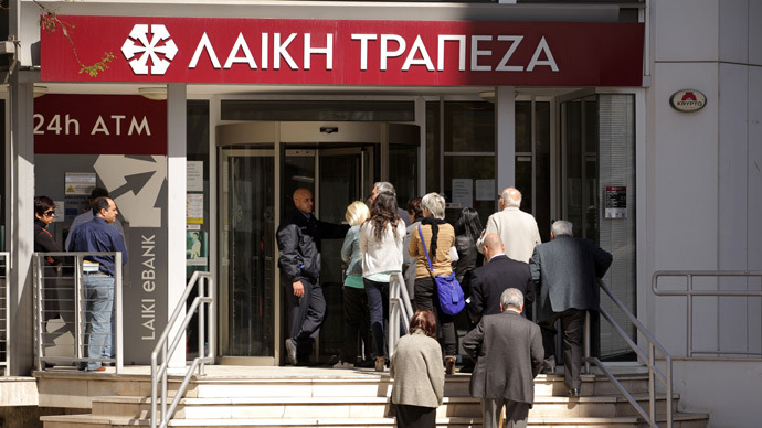 A security guard stands at the entrance of a branch of the Cyprus Popular Bank, Laiki as people queue up (AFP Photo / Patrick Baz)