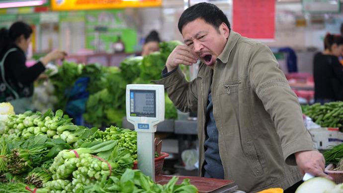 A vegetable seller waits for customers in a wet market in Shanghai on April 15, 2013. (AFP Photo / Peter Parks)