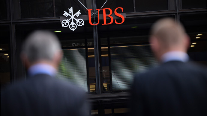 Businessmen walk towards the offices of Swiss bank UBS (AFP Photo / Carl Court)