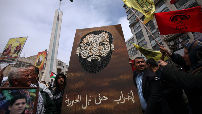 Palestinian protesters hold a placard with a portrait made from bread of Samer Issawi, a Palestinian prisoner who has been on a hunger strike for more than 250 days, during a gathering fence to mark Prisoners' Day in downtown Ramallah on April 17, 2013.(AFP Photo / Abbas Momani)