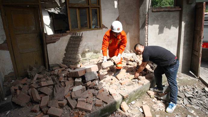 A rescuer helps a local resident remove debris from his house in a village in Qionglai township, after a shallow earthquake at magnitude 7.0 hit the city of Ya'an, in southwest China's Sichuan province on April 20, 2013 (AFP Photo)