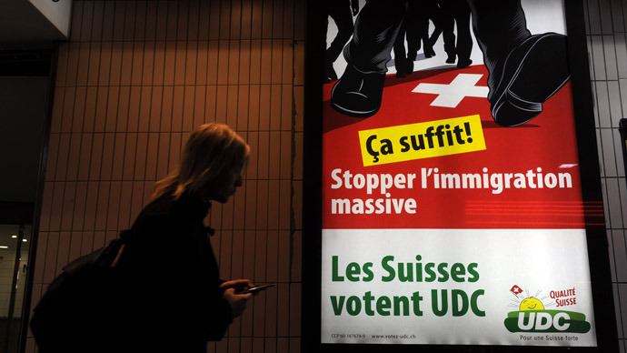 "A woman walks past a far-right UDC-VPC party poster reading ""Enough !, Stop massive immigration"" in Lausanne (AFP Photo)"