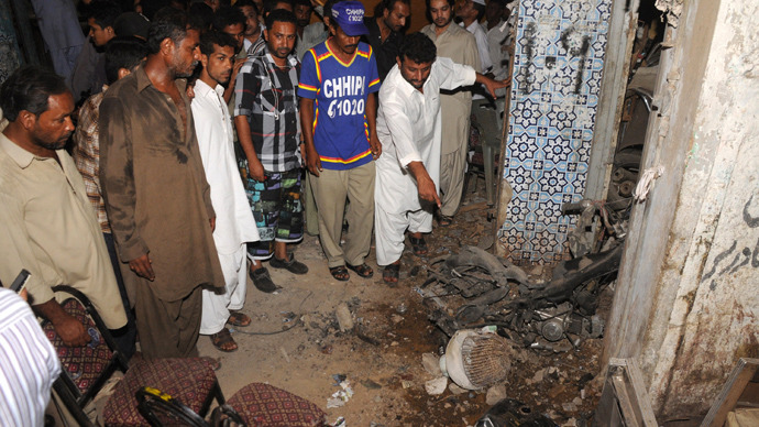 Supporters of Pakistan People's Party (PPP) observe the damage at the site of a bomb explosion in Karachi on April 27, 2013 (AFP Photo / Asif Hassan)