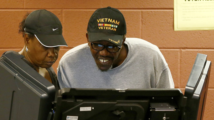 A voter (R) looks over his ballot as he participates in early voting at a polling place in Charlotte, North Carolina October 27, 2012. (ReutersChris Keane)