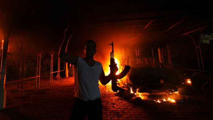 A protester reacts as the U.S. Consulate in Benghazi is seen in flames during a protest by an armed group said to have been protesting a film being produced in the United States September 11, 2012.(Reuters / Esam Al-Fetori)