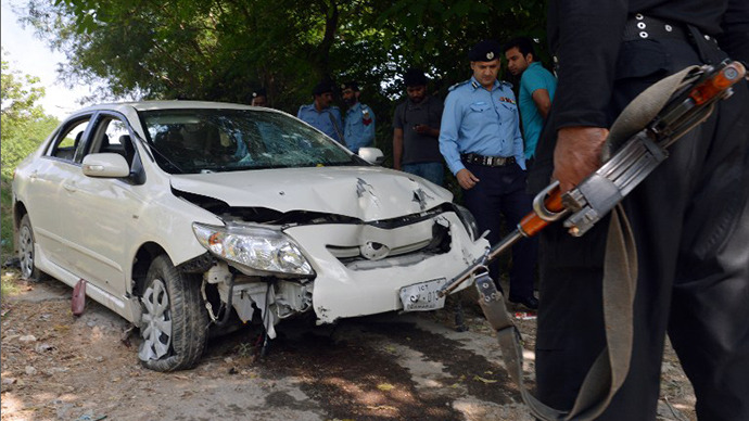 Pakistani police officials examine the bullet-riddled car of a slain government prosecutor Chaudhry Zulfiqar after an attack by gunmen in Islamabad on May 3, 2013. (AFP Photo / Aamir Qureshi)