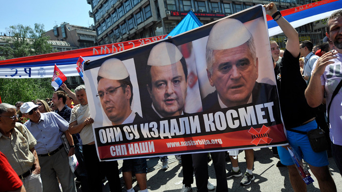 Demonstrators hold a poster showing mock images of Serbian top officials wearing traditional Albanian hats during a protest against the accord on the normalisation of relations between Serbia and Kosovo in the Serbian capital Belgrade on May 10, 2013 (AFP Photo / Andrey Isakovic)