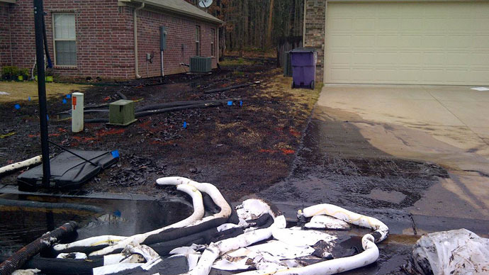 Spilt oil from Exxon pipeline runs between homes in North Woods Subdivision in Mayflower, Arkansas in this March 31, 2013 photo released to Reuters on April 11, 2013.(Reuters / Handout)