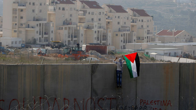 A Palestinian protester places a flag on the controversial Israeli barrier during clashes with Israeli security officers (unseen) after a rally marking the 48th anniversary of the founding of the Fatah movement, in the West Bank village of Bilin near Ramallah (Reuters / Ammar Awad )