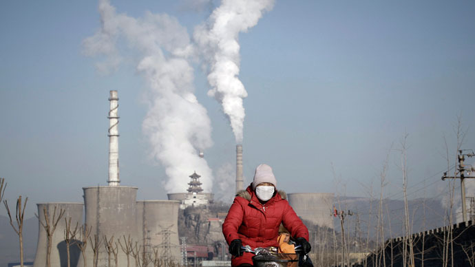 A woman wearing a mask rides past smoking chimneys and cooling towers of a steel plant in Beijing.(Reuters / Suzie Wong)