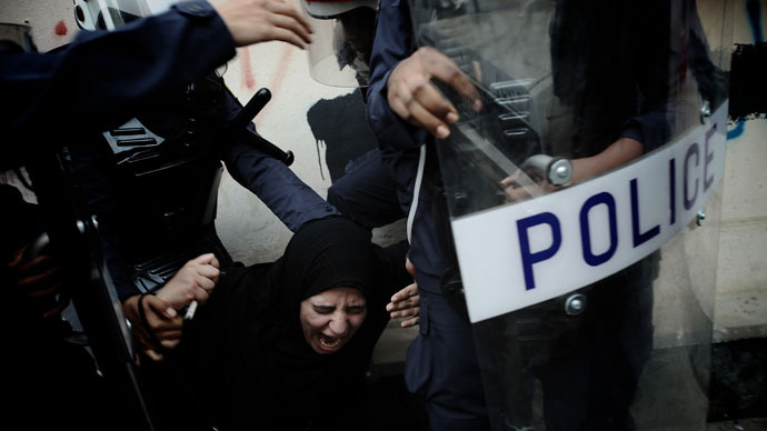 A Bahraini Shiite protester reacts as she is detained by riot police during an anti-government demonstration in the centre of the capital Manama on September 21, 2012.(AFP Photo / Mohammed Al-Shaikh)