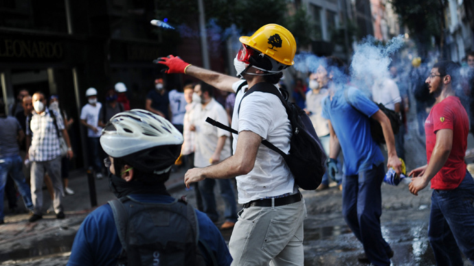 A protester throws back a tear gas canister at riot police during clashes between police and demonstrators in the streets adjacent to Taksim square in Istanbul, on June 16, 2013 (AFP Photo / Bulent Kilic)