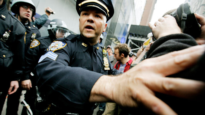 Members of the New York Police Department (NYPD) scuffle with protestors as they guard the entrance to a Citibank as Occupy Wall Street demonstrators march along 42nd Street to protest various businesses during May Day on May 1, 2012 in New York.(AFP Photo / Monika Graff)