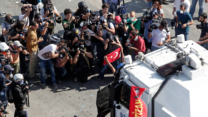 Media takes images of a protester holding a flag in front of a riot police vehicle during a protest at Taksim Square in Istanbul (Reuters / Osman Orsal)