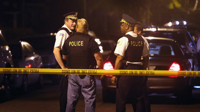 Police investigate the scene where a 16-year-old boy was shot and killed by police after he reportedly pointed a gun at officers during a foot chase on June 17, 2013 in Chicago, Illinois. (AFP Photo / Getty Images / Scott Olson)