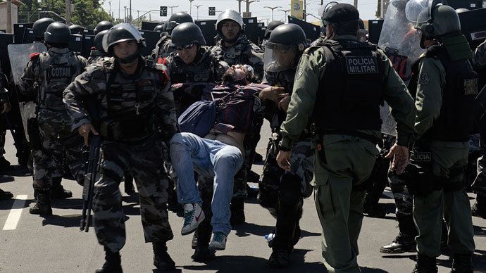 Anti-riot police officers carry a wounded demonstrator as clashes erupt in Fortaleza on June 19, 2013.(AFP Photo / Yuri Cortez)