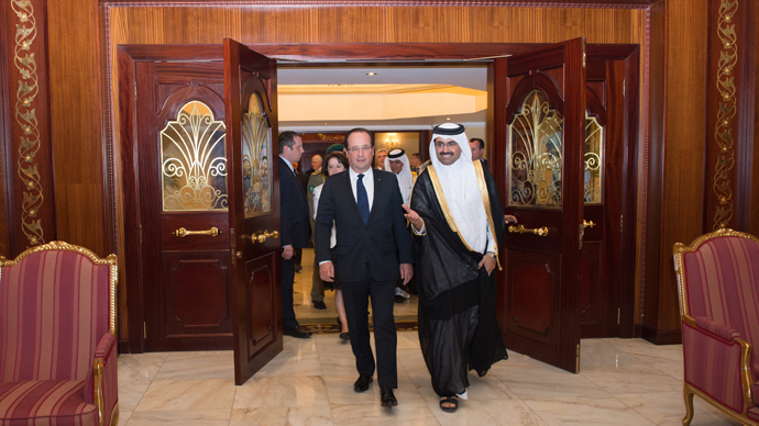 France's President Francois Hollande (C) and his companion Valerie Trierweiler (unseen) are welcomed by Qatar's Energy Minister Mohammed bin Saleh Al-Sada (R) at the airport as part of a two-day official visit to Doha on June 22, 2013 (AFP Photo / Bertrand Langlois)
