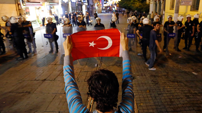 A protester holds the Turkish flag in front of a riot police line near Taksim Square in Istanbul June 22, 2013 (Reuters / Marko Djurica)