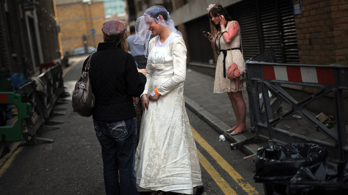 A man wearing a wedding dress speaks with other royal supporters during a wedding street party in London.(AFP Photo / Dinitar Dilkoff)