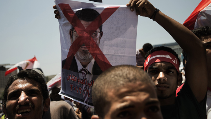 An Egyptian opposition supporter holds a crossed-out picture of President Mohammed Morsi as hundreds gather for a demonstration against Morsi and the Muslim Brotherhood in Cairo's landmark Tahrir Square on June 29, 2013 (AFP Photo / Gianluigi Guercia)