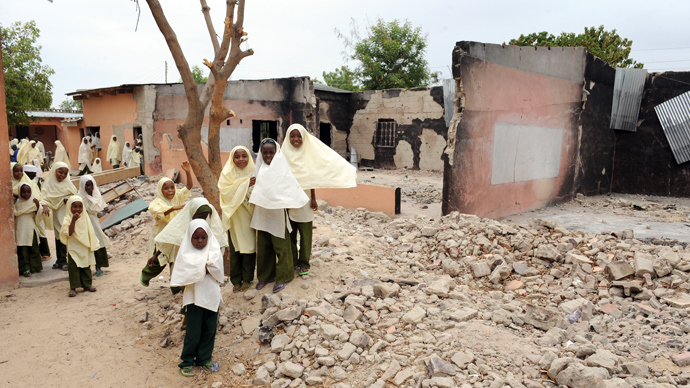School pupils play beside the burnt main auditorium of Maiduguri Experimental School, a private nursery, primary and secondary school burnt by the Islamist group Boko Haram to keep children away from school in Maiduguri, northeastern Nigeria (AFP Photo)