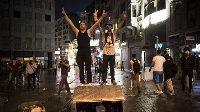 "Turkish protestors flash the ""V"" sign for victory as they stand on a trash bin during a protest in Istiklal avenue, in Istanbul on July 8, 2013. (AFP Photo / Behrouz Mehri)"
