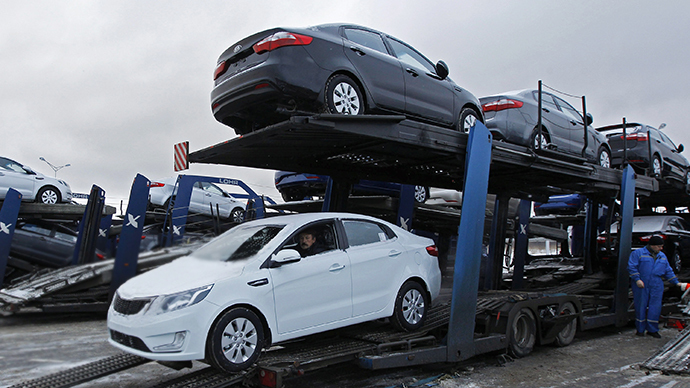 An employee drives a new car onto a transporter at the Hyundai factory outside St.Petersburg (Reuters / Alexander Demianchuk)