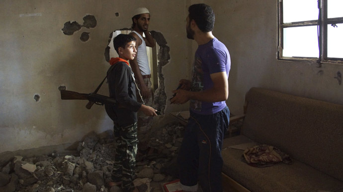 Dany, a 14-year-old fighter, whom activists say is the youngest fighter in the Khadraa brigade operating under the Free Syrian Army, chats with his fellow fighters in Deir al-Zor July 9, 2013. Picture taken July 9, 2013. (Reuters/Khalil Ashawi)