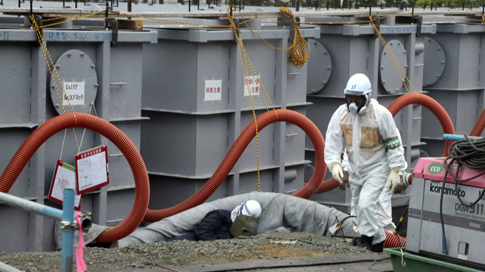 A worker walks in front of water tanks at Tokyo Electric Power Company's (TEPCO) tsunami-crippled Fukushima Daiichi nuclear power plant in Fukushima prefecture June 12, 2013. (Reuters/Noboru Hashimoto)