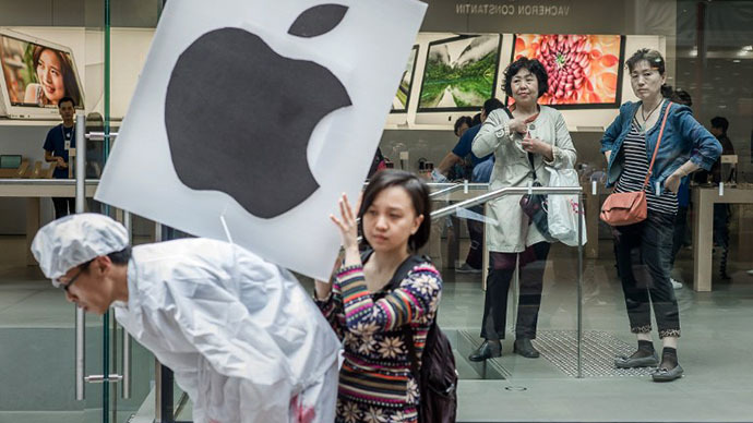 A protester holds a placard with an Apple logo on the back of a demonstrator dressed as a Chinese worker as two customers look on from inside a Apple store in Hong Kong on February 26, 2013. (AFP Photo / Philippe Lopez)