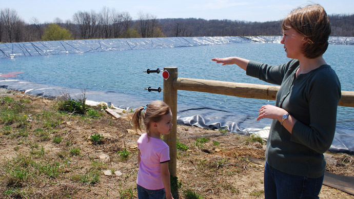 Stephanie Hallowich (R) and her daughter Alison look out over a three-acre reservoir supplying water to natural gas-drilling operations around her house in Hickory, Pennsylvania April 23, 2009. (Reuters/Jon Hurdle)