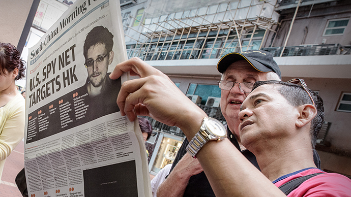 Two men read an edition of the South China Morning Post carrying the story of former US spy Edward Snowden (C) on its front page in Hong Kong on June 13, 2013. (AFP Photo / Philippe Lopez)