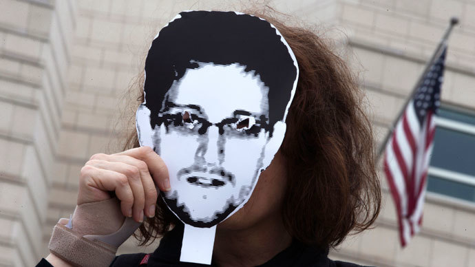 A woman holds a portrait of former U.S. spy agency contractor Edward Snowden in front of her face as she stands in front of the U.S. embassy during a protest in Berlin.(Reuters / Thomas Peter)