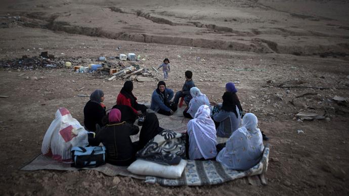 Bedouin women from al-Turi family sit next to their destroyed homes in the village of al-Akarib in the Negev Desert (AFP Photo / Menahem Kahana)