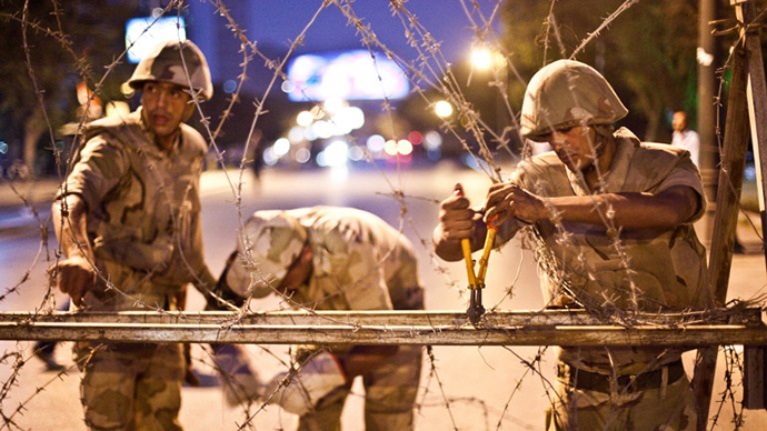 Egyptian army soldiers take out barbed wire that was surrounding the Supreme Constitutional Court in Cairo ahead of planned demonstrations on August 18, 2013. (AFP Photo / Virginie Nguyen Hoang)