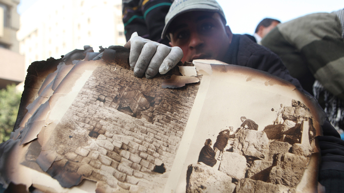 "A worker displays pages from the ancient document ""Le Description de L'Egypt"" salvaged from the ruins of the Scientific Institute of Egypt near Tahrir Square in Cairo (Reuters / Amr Abdallah Dalsh)"