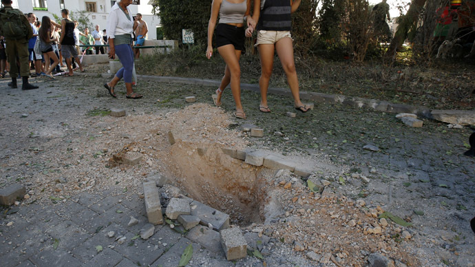 Onlookers walk past damage caused by a rocket fired from Lebanon into Israel, in Kibbutz Gesher HaZiv, near the northern city of Nahariya August 22, 2013. (Reuters/Ronen Zvulun)