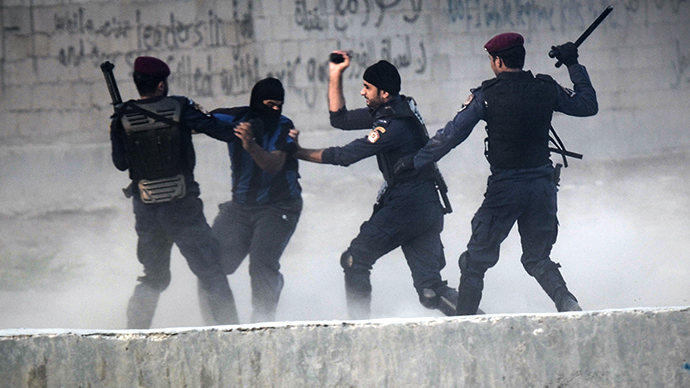 Bahraini police force arrest a protester during demonstration against the ruling regime in the village of Shakhora, west of Manama, on August 14, 2013. (AFP Photo / Mohammed Al-Shaikh)