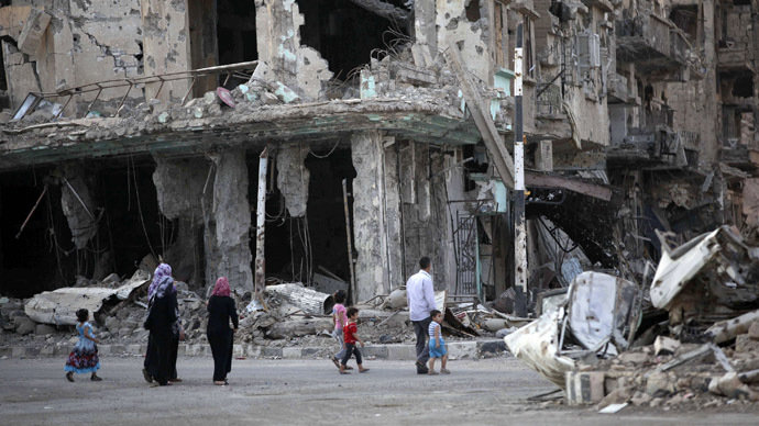 People walk along a damaged street filled with debris in Deir al-Zor September 4, 2013. (Reuters/Khalil Ashawi)